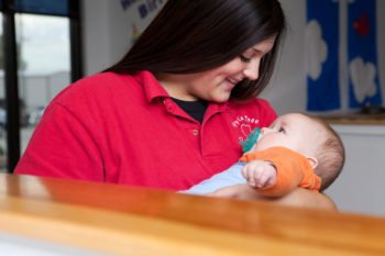 Caring infant daycare staff member at the Papillion location