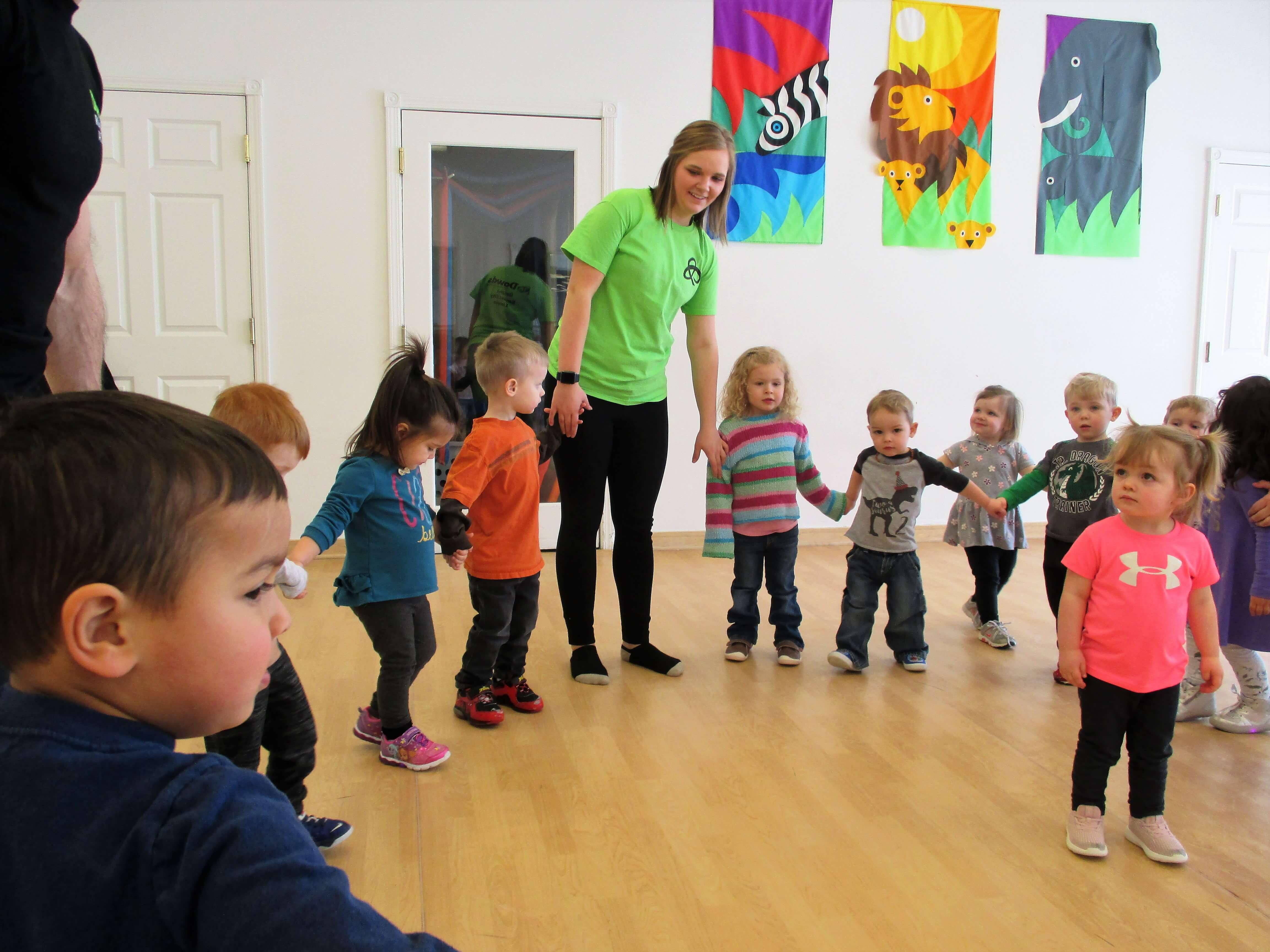 Preschool teacher holding hands with children in a circle