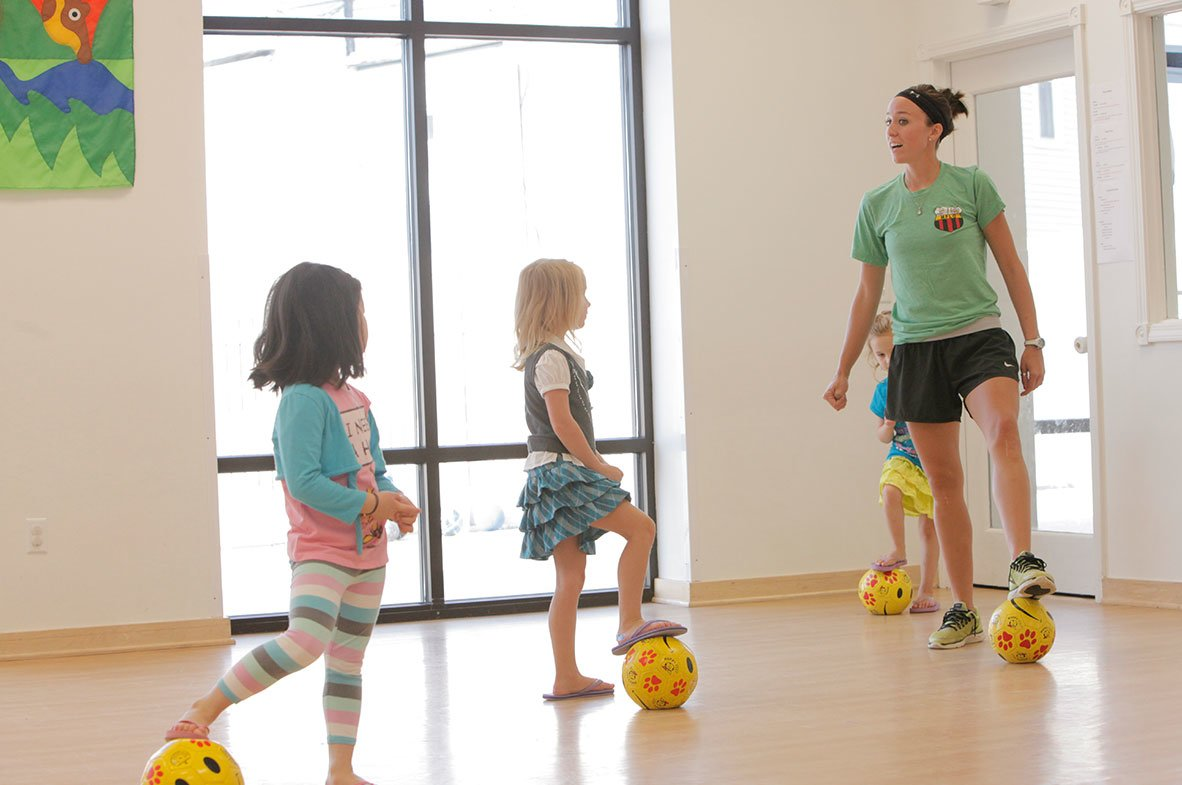 children playing soccer in an indoor gym