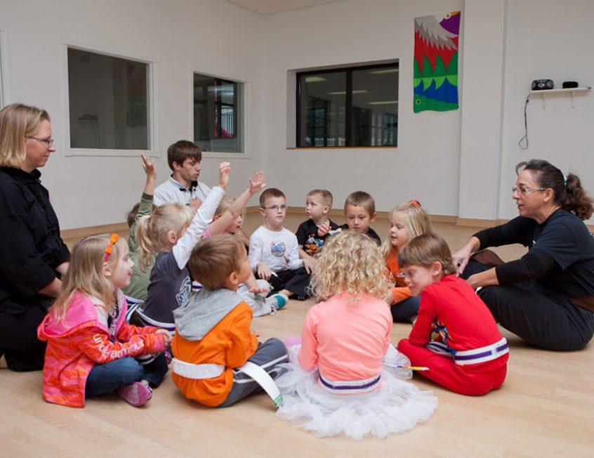 children sitting in a circle raising their hands
